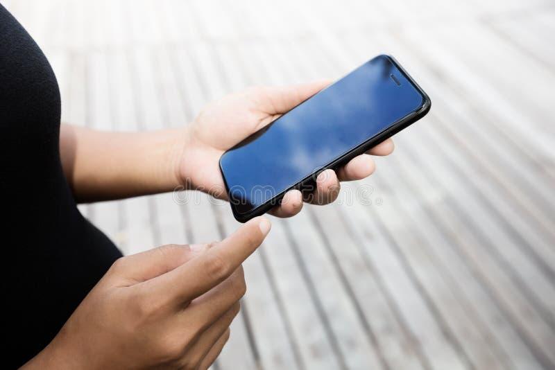 Крупный план на руке женщины используя образ жизни телефона внешний стоковые фото
