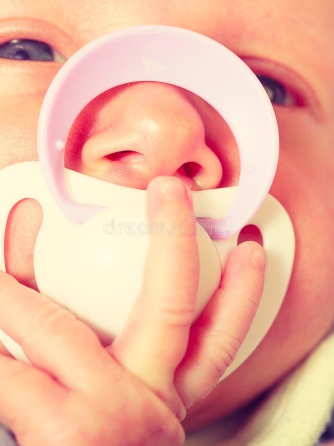 Крупный план немногого newborn лежать с центриком в рте стоковые изображения
