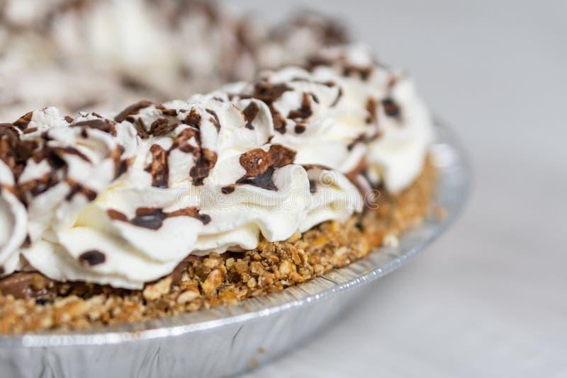 Крупный план очень вкусного кремового пирога готовый к серверу, отбензиниванию сливк и шоколада стоковое изображение