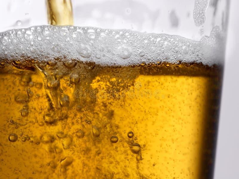 Крупный план пива золота золота янтарного лить в ясное стекло стоковые изображения
