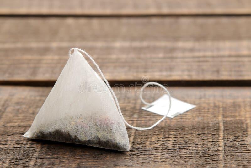 Крупный план пирамиды пакетика чая на коричневом деревянном столе Космос для текста стоковое фото rf