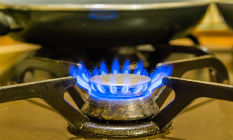 Крупный план плитаа освещенного газа, горя голубые пламена, винтажное оборудование кухни стоковая фотография