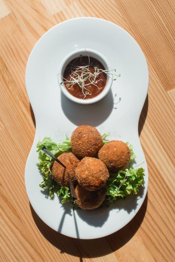 Крупный план плиты с испанскими croquettes служил с салатом и соусом стоковые изображения rf