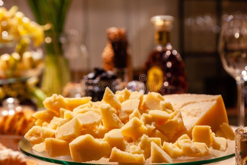 Крупный план плиты с частями итальянского пармезана на ресторанном обслуживание на представлении коньяка День рождения концепции, стоковое фото