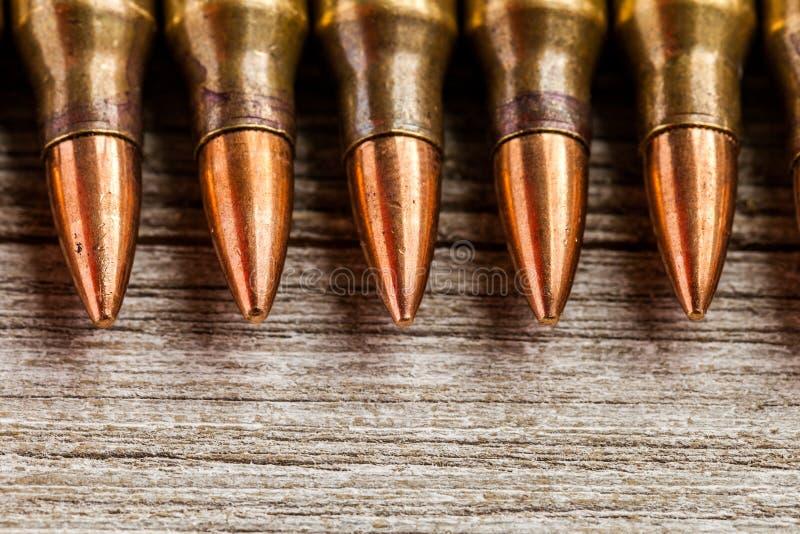 Крупный план пуль куртки металла винтовки полных в ряд на деревянной предпосылке с космосом экземпляра стоковые изображения