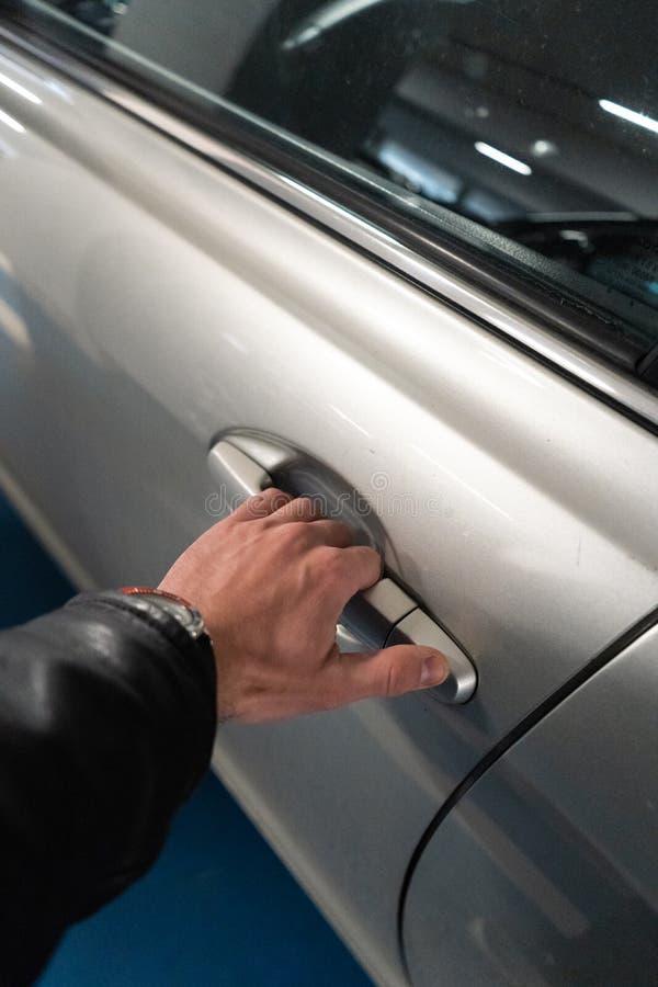 Крупный план рука людей на защелке автомобильной двери раскрывая ее вверх по - автомобилю светлого цвета стоковые изображения