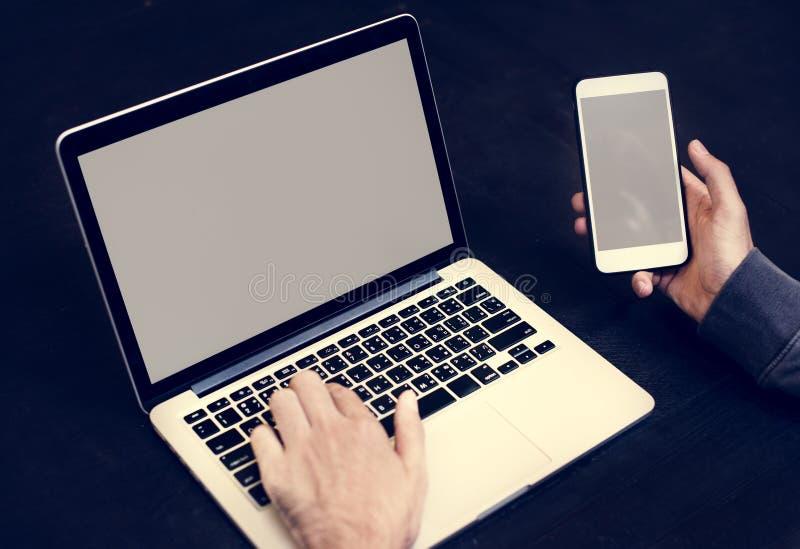 Крупный план руки держа мобильный телефон с предпосылкой компьтер-книжки компьютера стоковое фото rf