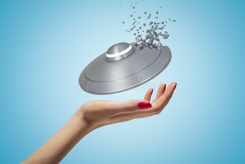 Крупный план руки женщины и маленького UFO над ее ладонью, одной стороны UFO начиная сломать в маленькие части, на свете бесплатная иллюстрация