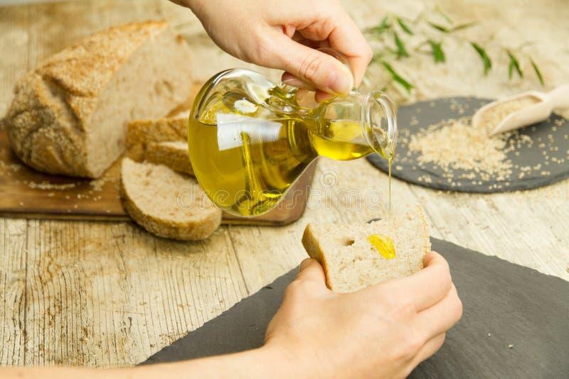 Крупный план рук женщины лить дополнительное девственное оливковое масло от ampule на куске домодельного хлеба в деревенском снят стоковые фото