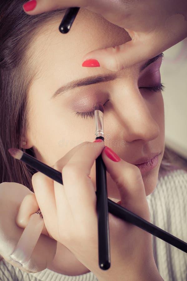 Крупный план рук прикладывая порошок теней для век на женской лицевой коже стоковые изображения