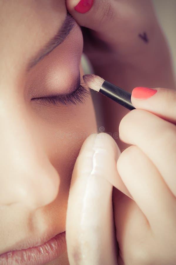 Крупный план рук прикладывая порошок теней для век на женской лицевой коже стоковые фотографии rf