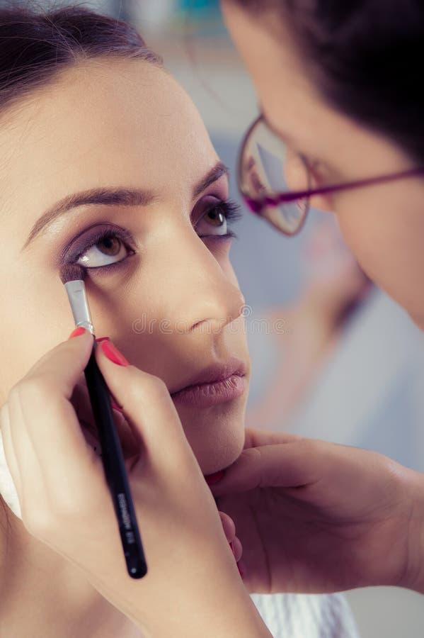 Крупный план рук прикладывая порошок теней для век на женской лицевой коже стоковые фото
