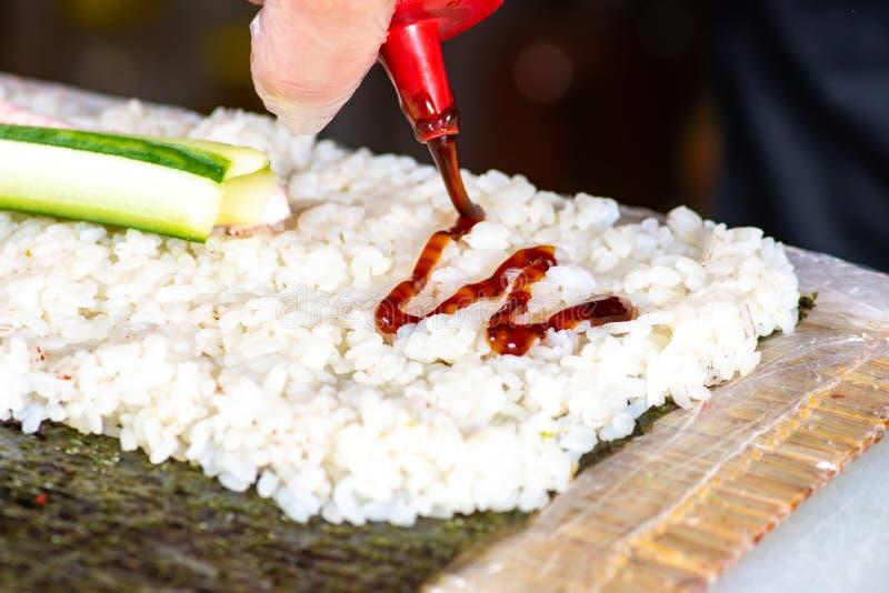Крупный план рук шеф-повара свертывая вверх по сушам на кухне, добавляя соус стоковые изображения rf