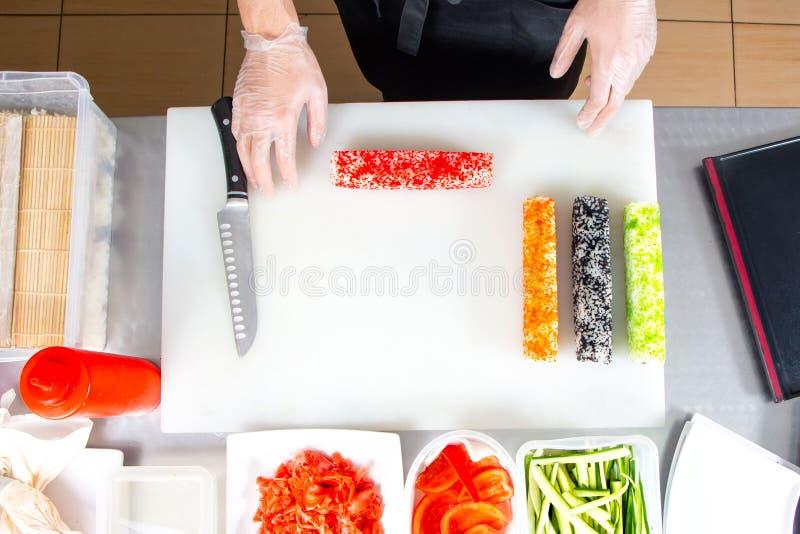 Крупный план рук шеф-повара свертывая вверх по сушам на кухне стоковая фотография rf