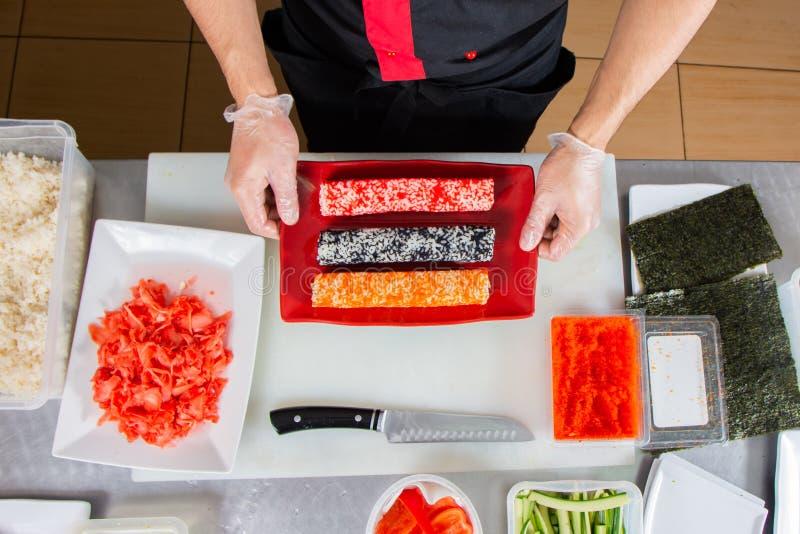 Крупный план рук шеф-повара свертывая вверх по сушам на кухне стоковое фото