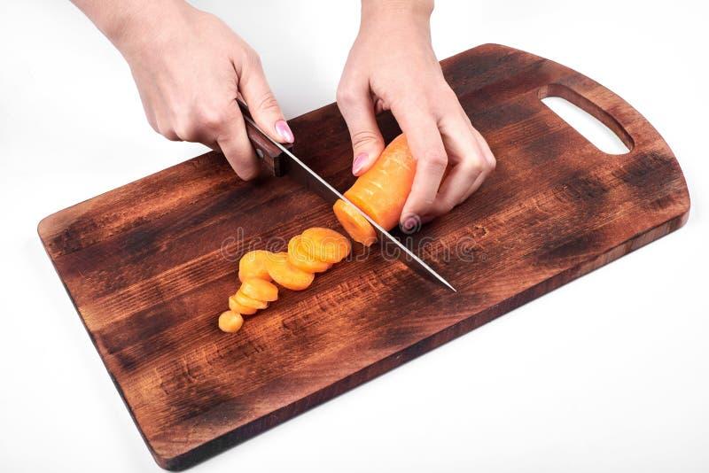 Крупный план рук ` s кашевара женщины, отрезая морковь на деревянной доске, изолированной на белой предпосылке стоковые фотографии rf