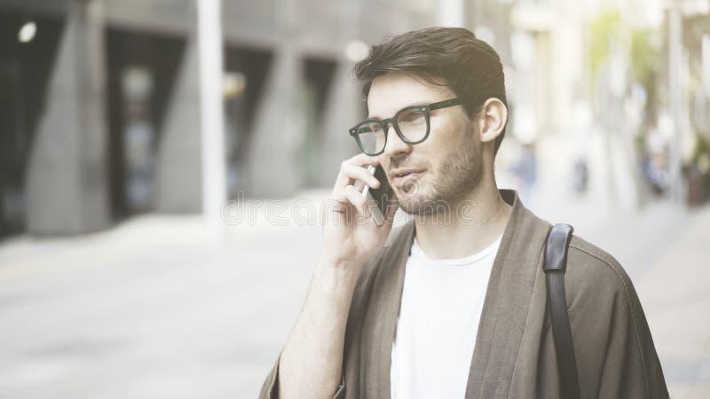 Крупный план серьезного молодого человека имея звонок на улице стоковые изображения rf