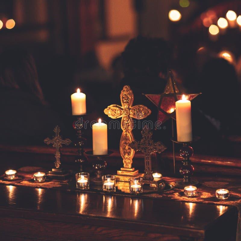 Крупный план снятый освещенных свечей и крестов на таблице стоковое фото