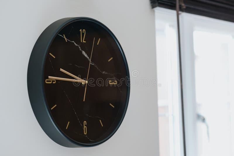 Крупный план снятый черных часов на белой стене внутри современного дома стоковое фото rf