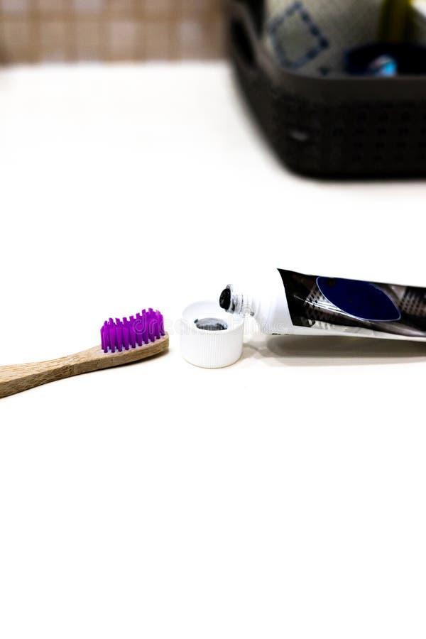 Крупный план, состав с бамбуковым toothbrushe, зубной пастой tblack на белой предпосылке стоковая фотография