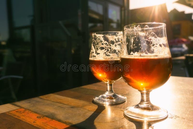 Крупный план 2 стекел пива на таблице террасы с солнцем вечера светя через их Релаксация, еда и концепция напитка с стоковая фотография