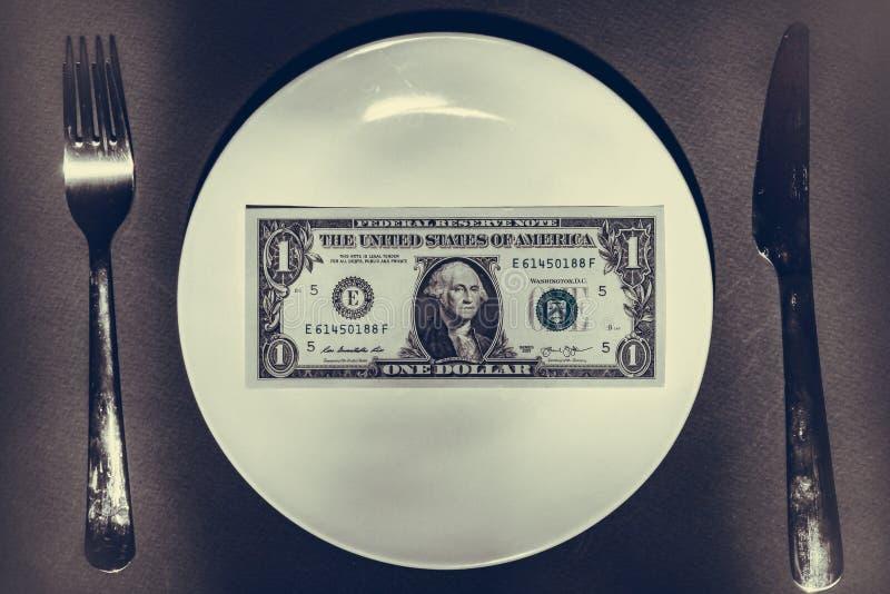 Крупный план стога наличных денег на белой плите с silverware стоковое фото