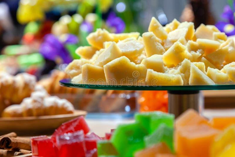 Крупный план стогов небольших кубов зеленого, красного, желтого, оранжевого мармелада, стеклянной круглой плиты с трудным сыром п стоковая фотография