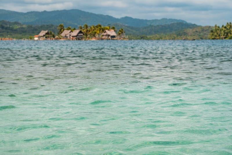 Крупный план текстуры воды океана с островом и деревянным backgr домов стоковые фото