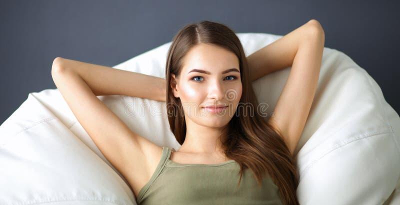 Крупный план усмехаясь молодой женщины лежа на кресле стоковые изображения rf