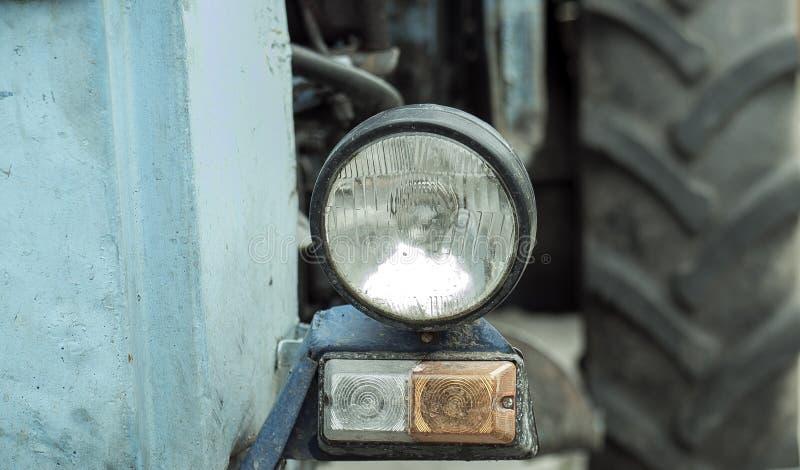 Крупный план фары на тракторе Половина старого ржавого зеленого исторического винтажного трактора с светлой загородкой автошины и стоковое фото