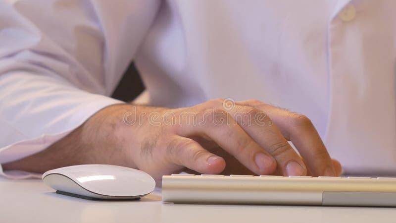 Крупный план человека используя компьютер Его рубашка и связь в предпосылке стоковое фото