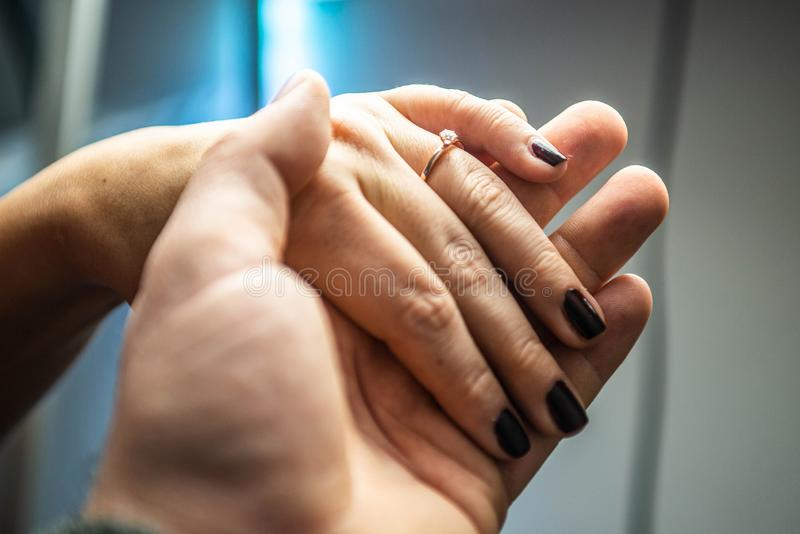Крупный план человека рук устанавливая обручальное кольцо в пальце женщины для замужества любов стоковое изображение