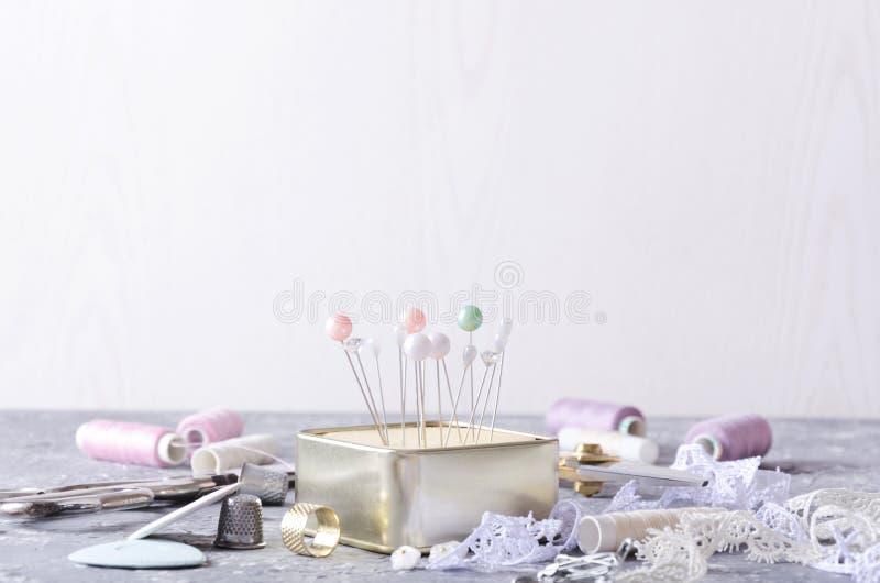 Крупный план шить штырей и pincushion, потока, ножниц и других шить инструментов на серой таблице против белой предпосылки m стоковая фотография rf