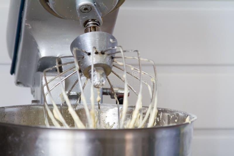 Крупный план электрического смесителя с взбитым ровным тестом для торта Поколотите быть взбитым Смешивая белое тесто в шаре со см стоковые фотографии rf