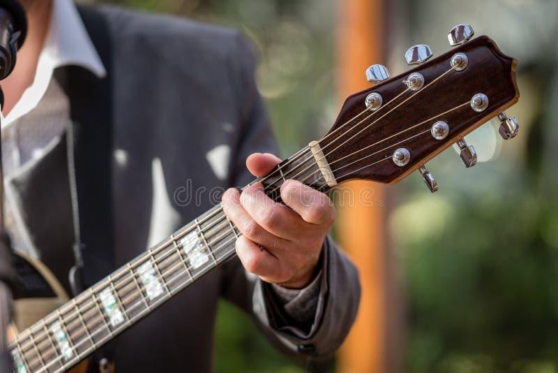 Крупный план ` s человека вручает играть акустическую гитару Музыкальная принципиальная схема стоковая фотография rf