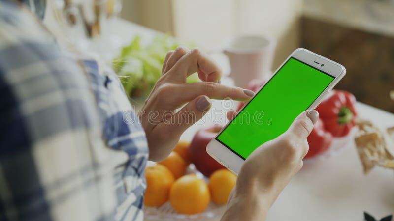 Крупный план smartphone просматривать руки ` s женщины с зеленым экраном на кухне дома стоковое фото rf