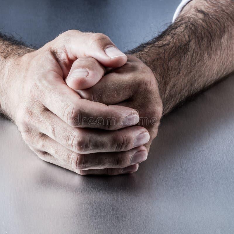 Крупный план, анонимные расслабленные мужские волосатые руки держа совместно на столе стоковое изображение