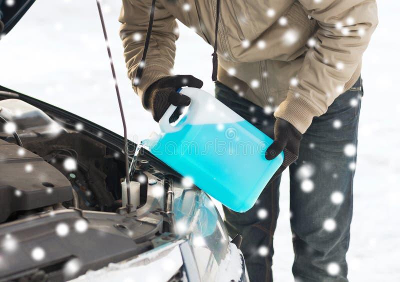 Крупный план антифриза человека лить в автомобиль стоковое фото