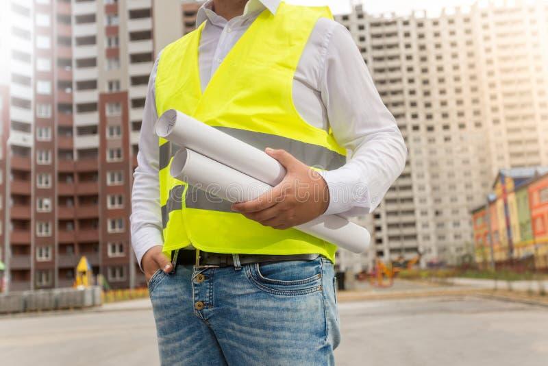 Крупный план архитектора в жилете безопасности представляя с светокопиями на ne стоковое изображение