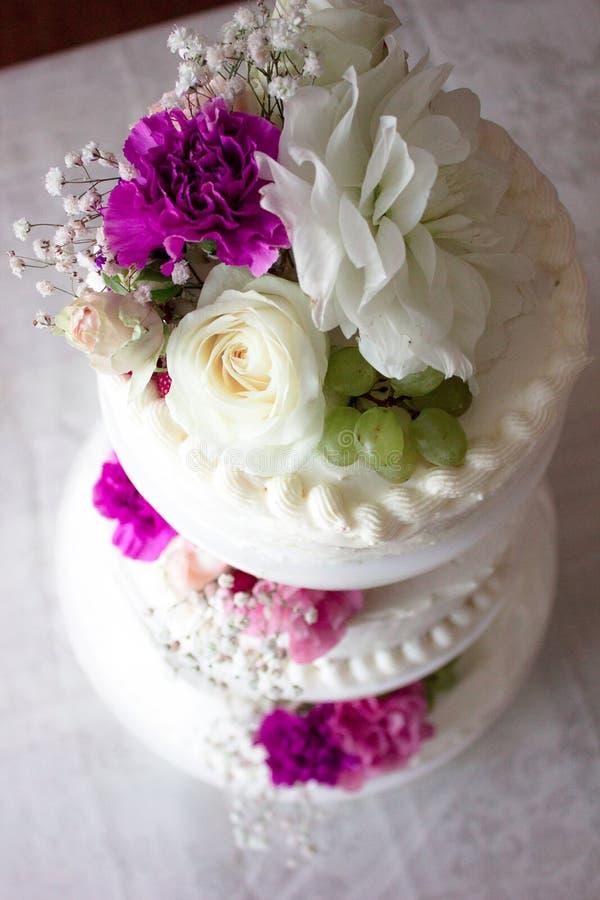 Крупный план белого свадебного пирога с коричневой лентой и цветков на верхней части стоковая фотография rf