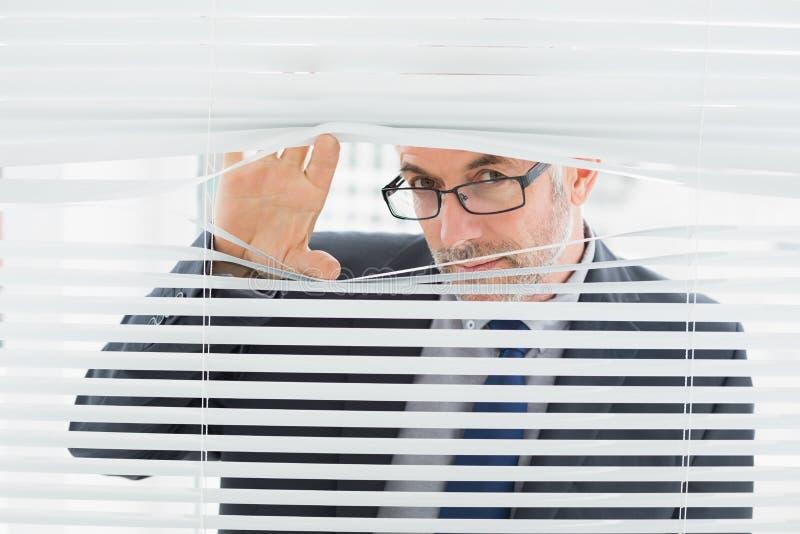 Крупный план бизнесмена peeking через шторки в офисе стоковая фотография rf