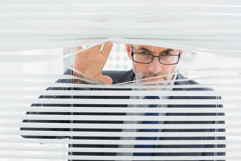 Крупный план бизнесмена peeking через шторки в офисе стоковые фото