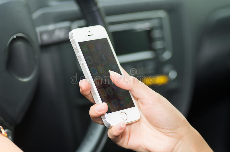 Крупный план внутри корабля руки держа smartphone, рулевое колесо и черную внутреннюю предпосылку, женскую концепцию водителя стоковая фотография