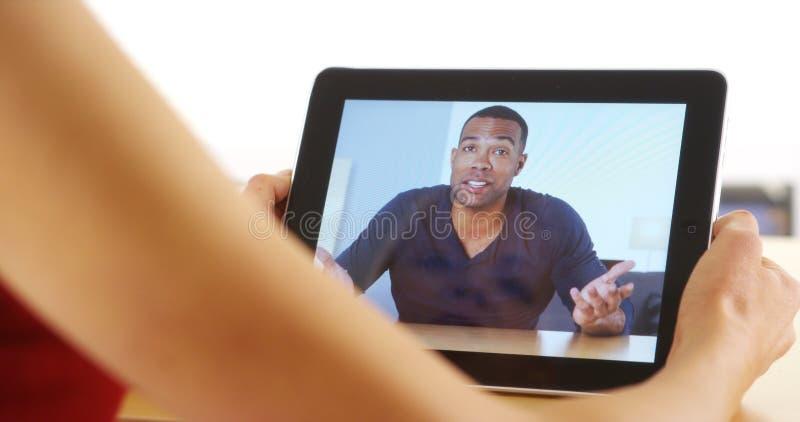 Крупный план вскользь черного бизнесмена говоря на таблетке стоковая фотография rf