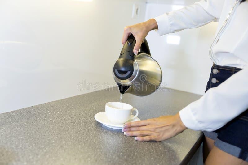 Крупный план горячей воды будучи политым из чайника стоковое изображение rf