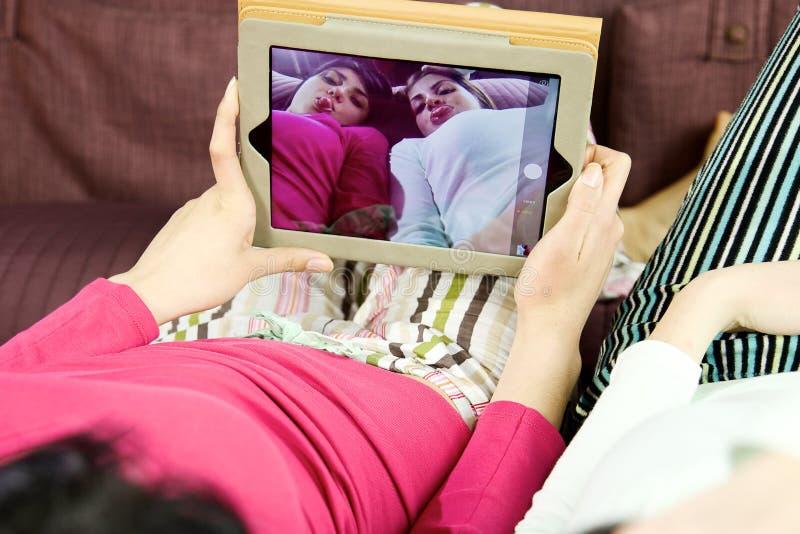 Крупный план девушек играя фотографируя с таблеткой стоковое изображение rf