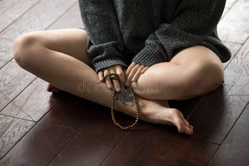 Крупный план женских ног в представлении Sukhasana, предпосылке студии просторной квартиры стоковое фото