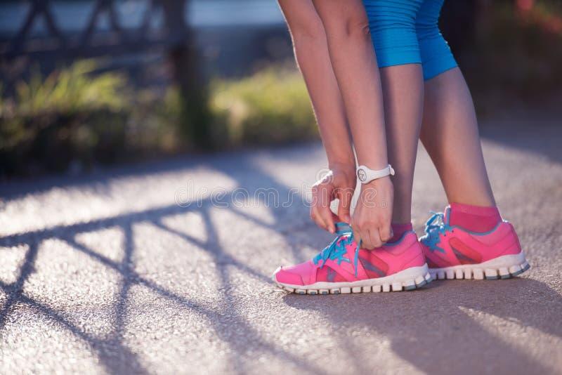 Крупный план женщины связывая идущий ботинок стоковое изображение