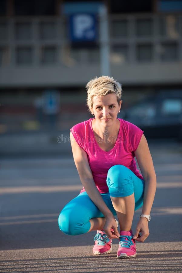 Крупный план женщины связывая идущий ботинок стоковая фотография rf