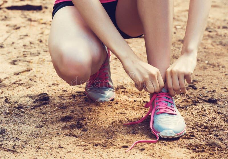 Крупный план женщины связывая шнурки ботинка Женский бегун фитнеса спорта получая готовый для jogging outdoors на пути леса i стоковые изображения